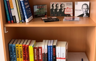 """Bücher im Regal bei Capron, darunter """"Komm zum Punkt!"""" von Thilo Baum"""