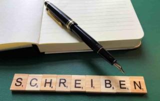 """Ein Notizbuch, ein Füller auf einem Schreibtisch. Daneben Scabble-Buchstaben mit dem Wort """"Schreiben"""""""